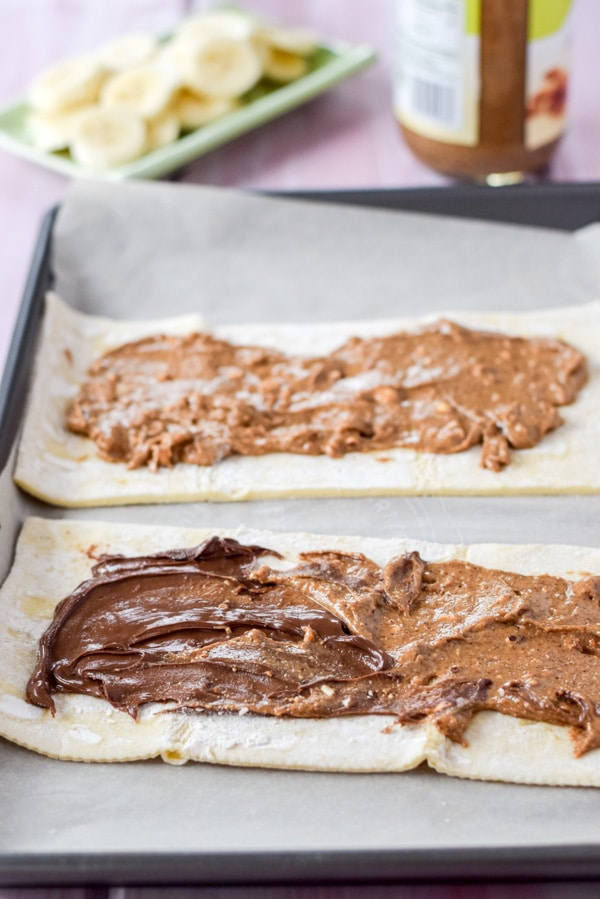 Almond butter and Nutella spread on a puff pastry sheet