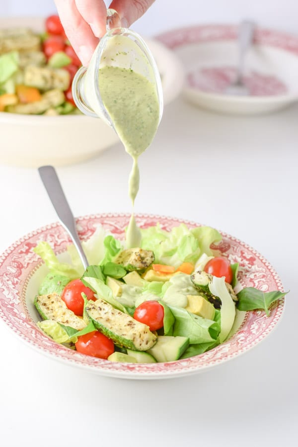 Pouring dressing on the beautiful Boston Lettuce Vegetable salad