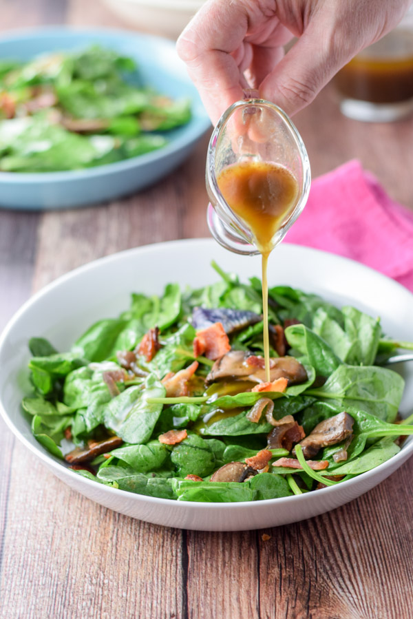 Vinaigrette getting poured on the super tasty spinach salad