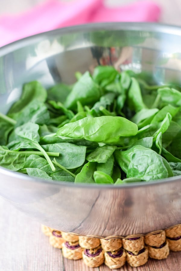 Spinach in a bowl ready to be made into the super tasty spinach salad