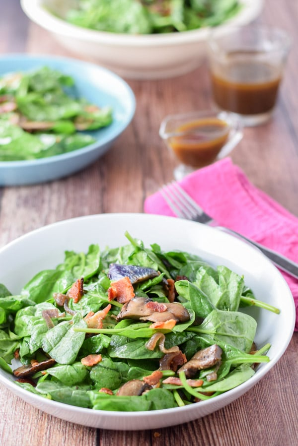 Super tasty spinach salad served in bowls with vinaigrette dressing in the background