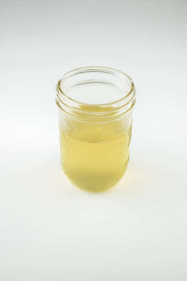 A container of easy ginger infused simple syrup