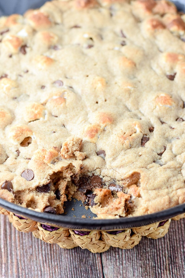 Close up of a chunk of toasted marshmallow chocolate chip skillet cookie taken out of the pan